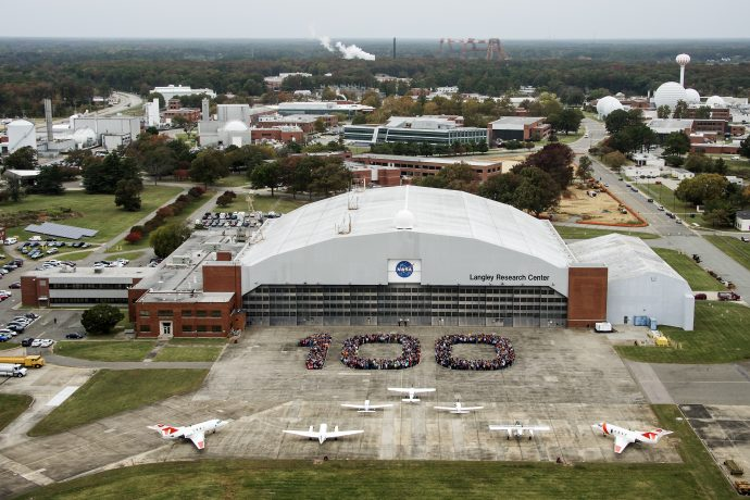 Aerial photos of NASA Langley employees gathered on the back ramp in the shape of 100.